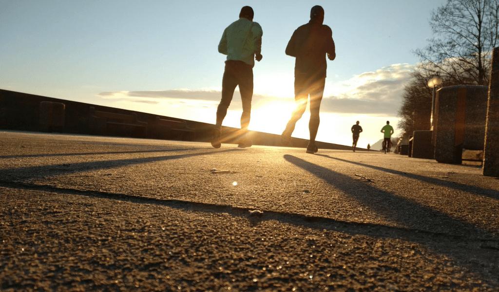 Vier Jogger laufen bei Sonnenuntergang eine Promenade entlang.