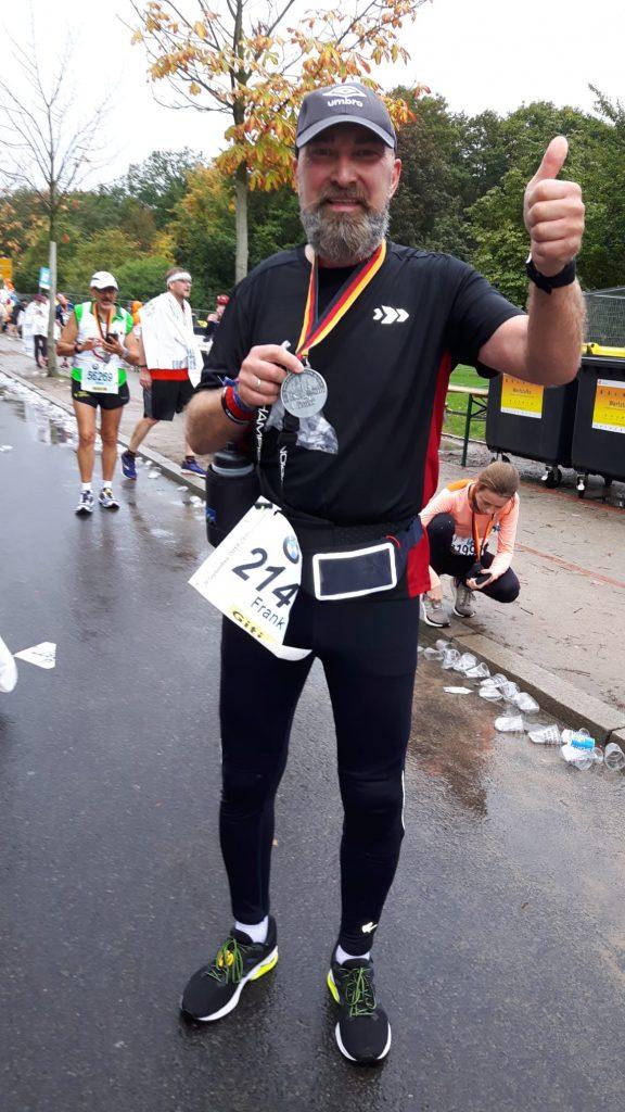 Ein Mann im Sportoutfit hält seine Marathon-Medaille ins Bild
