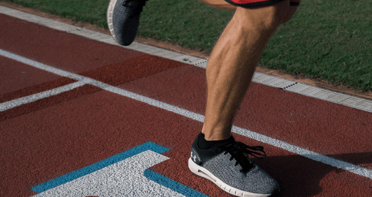 Ein Mann in Sportschuhen läuft auf einer Tartanbahn